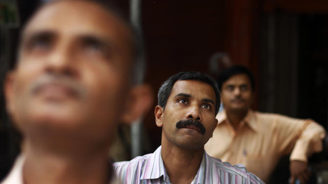Indians watch a screen on the facade of the the Bombay Stock Exchange (BSE) building in Mumbai, India, Monday, June 18, 2012. India's central bank left its key interest rate unchanged Monday due to inflation concerns, thwarting hopes of a rate cut to kickstart flagging growth in Asia's third-largest economy. (AP Photo/Rafiq Maqbool)