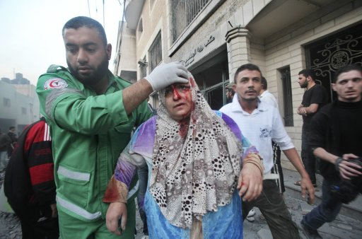 A Palestinian medic helps evacuate a wounded woman after an Israeli air strike in Gaza City