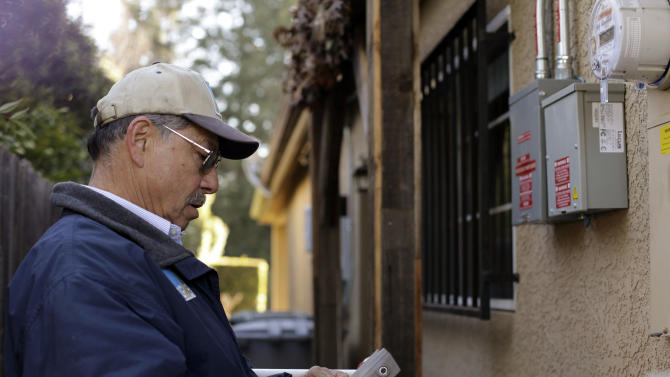 In this Friday, Jan. 11, 2013 photo, PG&E employee Art Liscano, 66, reads a meter at a house in Clovis, Calif. Liscano's department employed 50 full-time meter readers just six years ago. Now, it has six. (AP Photo/Gosia Wozniacka)