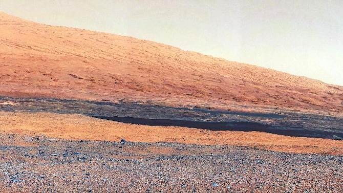 """In this image released by NASA on Monday, Aug. 27, 2012, a photo taken by the Mast Camera (MastCam) highlights the geology of Mount Sharp, a mountain inside Gale Crater, where the rover landed. Prior to the rover's landing on Mars, observations from orbiting satellites indicated that the lower reaches of Mount Sharp, below the line of white dots, are composed of relatively flat-lying strata that bear hydrated minerals. Those orbiter observations did not reveal hydrated minerals in the higher, overlying strata. The MastCam data now reveal a strong discontinuity in the strata above and below the line of white dots, agreeing with the data from orbit. Strata overlying the line of white dots are highly inclined (dipping from left to right) relative to lower, underlying strata. The inclination of these strata above the line of white dots is not obvious from orbit. This provides independent evidence that the absence of hydrated minerals on the upper reaches of Mount Sharp may coincide with a very different formation environment than lower on the slopes. The train of white dots may represent an """"unconformity,"""" or an area where the process of sedimentation stopped. (AP Photo/NASA/JPL-Caltech/MSSS)"""
