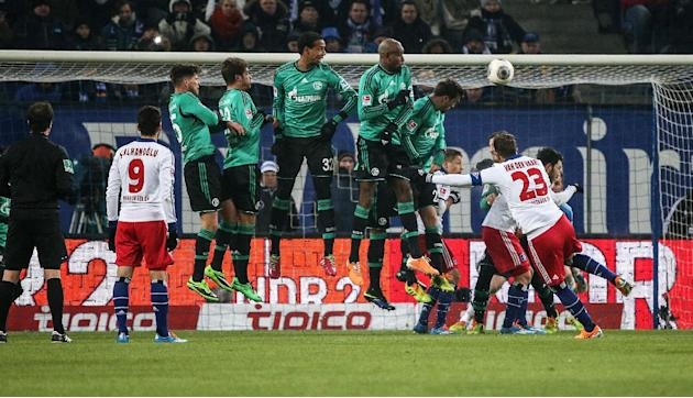 Hamburg's  Rafael van der Vaart, right, shoots a free kick during the German Bundesliga soccer match between Hamburger SV and Schalke 04, in Hamburg Germany, Sunday Jan 26, 2014