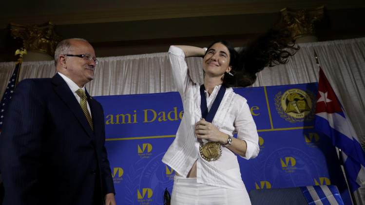 Blogger and activist Yoani Sanchez, of Cuba, right, adjusts her hair after receiving a medal from Miami Dade College president Eduardo Padron, left, after speaking at the Freedom Tower of Miami Dade College, Monday, April 1, 2013, in Miami. Sanchez has gained thousands of followers worldwide for her candid descriptions of modern life in Cuba on her blog Generation Y. (AP Photo/Lynne Sladky)