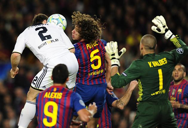 Chelsea's Serbian Defender Branislav Ivanovic (L) Amd Barcelona's Captain Carles Puyol (C) Jump For The Ball AFP/Getty Images