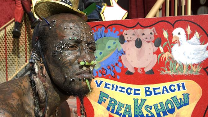 """This publicity image released by AMC shows Creature waiting for passerbys to come see the Venice Beach Freakshow on the boardwalk of Venice Beach, Calif. """"Freakshow,"""" is an unscripted series premiering Thursday at 9:30 p.m. EST on AMC. (AP Photo/AMC, Ron Jaffe)"""