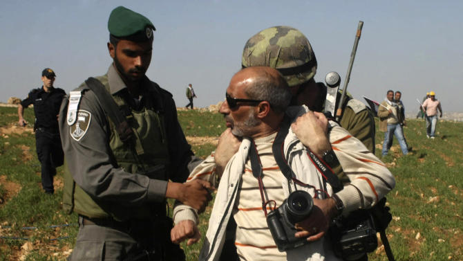 In this Saturday Feb. 9, 2013 photo, Israeli security detain The Associated Press photographer Nasser Shiyoukhi during a Palestinian protest in Yatta, West Bank. Israeli troops detained Shiyoukhi handcuffing him and forcing him to sit on the ground without food or water or access to a bathroom for roughly five hours, according to witness accounts. Shiyoukhi was released without charge after Saturday's incident. (AP Photo)