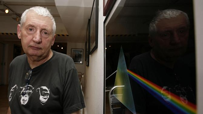 """FILE - This July 24, 2008 file photo shows English graphic designer Storm Thorgerson standing next to his album cover artwork for Pink Floyd's """"The Dark Side of the Moon"""" during the opening of his exhibition 'Mind Over Matter: The Images of Pink Floyd' in London. Storm Thorgerson whose eye-catching Pink Floyd and Led Zeppelin album covers captured the spirit of 1970s psychedelia, has died. He was 69. In a statement, Thorgerson's family said that he died Thursday April 18, 2013 and that """"his ending was peaceful and he was surrounded by family and friends."""" (AP Photo/PA, Yui Mok, File) UNITED KINGDOM OUT  NO SALES  NO ARCHIVE"""