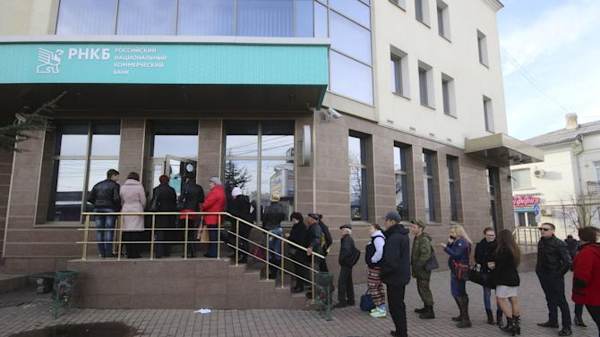 People stand in a line to use an ATM machine at a bank office in Simferopol