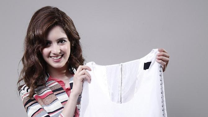 """In this March 13, 2012 photo, actress Laura Marano from Disney Channel's """"Austin & Ally,"""" poses with a blousoned white dress with a beaded metallic skirt while talking about prom fashion in New York. (AP Photo/Carlo Allegri)"""