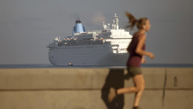 FILE - In this March 19, 2015, file photo, a woman jogs on the Malecon as the Thomson Dream cruise ship arrives in Havana bay. The Obama administration has approved on Tuesday, May 5, 2015, the first ferry service in decades between the United States and Cuba, potentially opening a new path for the hundreds of thousands of people and hundreds of millions of dollars in consumer goods that travel between Florida and Havana each year. (AP Photo/Desmond Boylan, File)