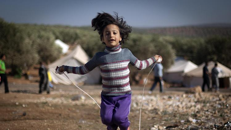 A Syrian girl who fled with her family from the violence in their village, jumps a rope at a displaced camp, in the Syrian village of Atma, near the Turkish border with Syria. Wednesday, Nov. 7, 2012.(AP Photo/ Khalil Hamra)