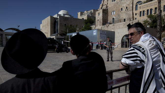 """A border police officer stands guard as ultra-Orthodox Jewish men look at the scene of a shooting at the plaza of the Western Wall, the holiest site where Jews can pray, in Jerusalem's old city, Friday, June 21, 2013. Israeli police say a guard has shot a Jewish man dead at the key Jerusalem holy site. Police spokesman Micky Rosenfeld says a private security guard at the Western Wall """"fired a number of shots"""" at a man who appeared suspicious. The guard told police the man, an Israeli, had his hands in his pockets and shouted in Arabic just before the guard opened fire, Rosenfeld said. The man, in his 40s, died at the scene. (AP Photo/Sebastian Scheiner)"""
