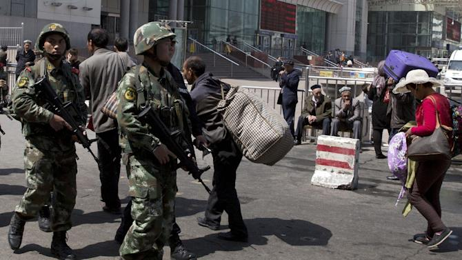 FILE - In this Thursday, May 1, 2014 file photo, heavily armed Chinese paramilitary policemen march past the site of an explosion outside the Urumqi South Railway Station in Urumqi, northwest China's Xinjiang Uygur Autonomous Region. China on Sunday, May 18, 2014 blamed a separatist militant group for carrying out the deadly attack at the station last month, underscoring Beijing's claims that the country faces a threat from an organized militancy with elements based overseas. (AP Photo/Ng Han Guan, File)