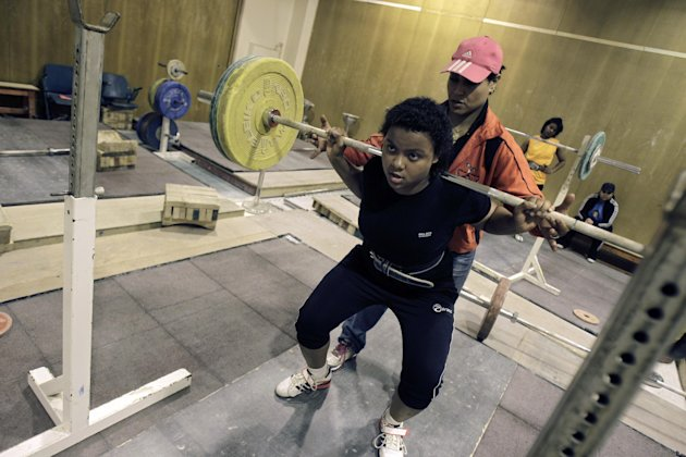 In this Monday, June 18, 2012 photo, Najwan El Zawawi, background, UAE women's weightlifter team coach, assists Khadija Mohammed, who competes in the 75-kilogram category and will be the first female lifter from the Gulf at the Olympics and the first Emirati to qualify for the Olympics outright, at the Al Shabab stadium in Dubai, United Arab Emirates. (AP Photo/Kamran Jebreili)