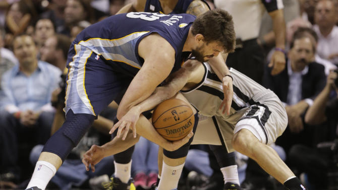 Memphis Grizzlies' Marc Gasol, left, and San Antonio Spurs' Manu Ginobili, of Argentina, battle for a loose ball during the first half in Game 2 of the Western Conference finals NBA basketball playoff series, Tuesday, May 21, 2013, in San Antonio. (AP Photo/Eric Gay)