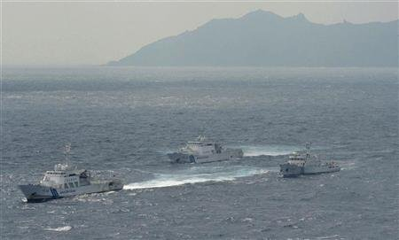 An aerial photo shows a Chinese marine surveillance ship Haijian No. 66 (R) cruising next to Japan Coast Guard patrol ships in the East China Sea, known as Senkaku isles in Japan and Diaoyu islands in China, in this photo by Kyodo September 24, 2012. REUTERS/Kyodo