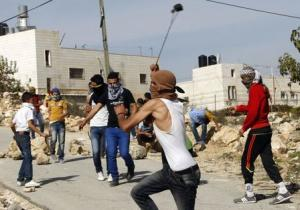 Palestinian uses a slingshot to throw stones toward Israeli soldiers during clashes in Siear town near the West Bank city of Hebron
