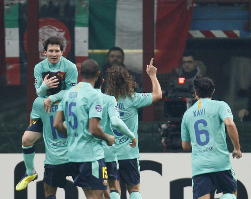 Barcelona forward Lionel Messi, top left, of Argentina, celebrates with his teammates after scoring during a Champions League, group H, soccer match between AC Milan and Barcelona at the San Siro stadium in Milan, Italy, Wednesday, Nov. 23, 2011. (AP Photo/Antonio Calanni)
