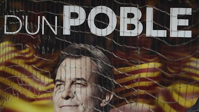 An electoral poster featuring the leader of center-right Catalan Nationalist Coalition (CiU) Artur Mas is seen in the street following Sunday's elections in Barcelona, Spain, Monday, Nov. 26, 2012. A day after voters in Spain's economically powerful region of Catalonia dealt a punishing blow to the ruling party advocating independence from Spain, the pressure was on the party leader and regional president Artur Mas to form a new government that would carry out his promise. (AP Photo/Manu Fernandez)