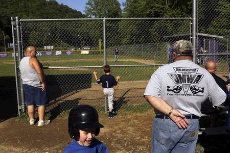 File picture shows retired coal miner Kenneth Douglas Sparks watching his son and grandson's Little League baseball game in Gilbert, Mingo County, West Virginia