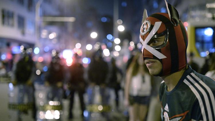 A masked fan walks in front of a line of Brazilian police in Copacabana after the final match between Germany and Argentina during the soccer World Cup in Rio de Janeiro, Brazil, Sunday, July 13, 2014. Mario Goetze volleyed in the winning goal in extra time to give Germany its fourth World Cup title with a 1-0 victory over Argentina. (AP Photo/Manu Fernandez)
