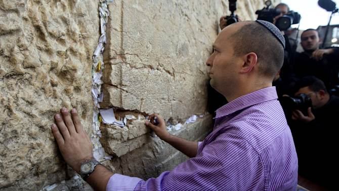 """FILE - In this Jan. 21, 2013 file photo, Naftali Bennett, head of the Jewish Home party, touches the stones of the Western Wall, the holiest site where Jews can pray, in Jerusalem's Old City. The idea of Palestinians establishing a state in the territory they seek has """"reached a dead end,"""" Naftali Bennett, economics minister, said Monday, June 17, 2013, in the latest remarks by hard-liners that appear to contradict the country's official support for a """"two-state solution"""" to its conflict with the Palestinians. (AP Photo/Sebastian Scheiner, File)"""