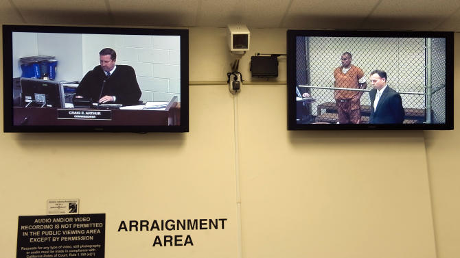 Video screens display Commissioner Craig Arthur, left, as he listens to attorneys at the arraignment of Marcos Sarinana Gurrola in Santa Ana, Calif., on Tuesday, Dec. 18, 2012. Gurrola was charged with 54 counts of discharging a gun in public and two counts of assault after opening fire outside Fashion Island mall. He was also charged with 10 more counts after prosecutors linked him to a similar shooting in 2011 at the same mall in Newport Beach. (AP Photo/The Orange County Register, Paul Bersebach)