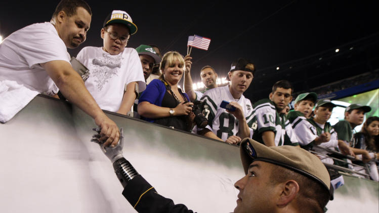 Medal of Honor recipient Army Ranger Leroy Petry, of New Mexico, shakes hands with spectators before an NFL football game between the Dallas Cowboys and the New York Jets Sunday, Sept. 11, 2011, in East Rutherford, N.J. (AP Photo/Julio Cortez)