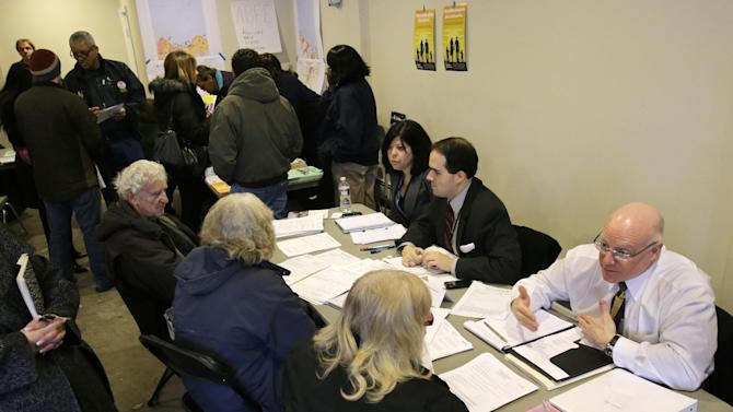 "New Jersey Department of  Banking and Insurance employee, Christian Traum, right, and workers from the Federal Emergency Management Agency and state agencies help residents at a center in Union Beach, N.J., Tuesday, Feb. 5, 2013. New Jersey Gov. Chris Christie said the National Flood Insurance Program's handling of claims in New Jersey has been ""a disgrace,"" complaining that the program has been far too slow to resolve claims from Superstorm Sandy, with 70 percent of cases unresolved three months after the disaster. (AP Photo/Mel Evans)"