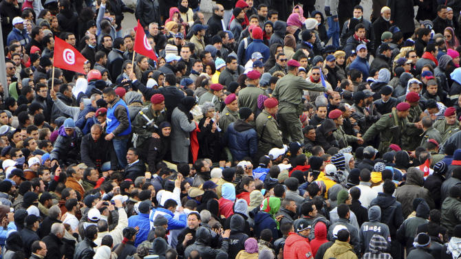 Thousands of Tunisians are gathered at el Jallez cemetery to attend the funerals of slain opposition leader Chokri Belaid, near Tunis, Friday Feb. 8, 2013. The Wednesday Feb. 6 assassination of prominent government critic Chokri Belaid plunged the country into one of its deepest political crises since the overthrow of the dictatorship in 2011. The coffin is carried by pallbearers at center of picture.(AP Photo/Hassene Dridi)