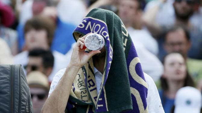James Ward of Britain takes a drink with a towel on his head during a break between games of his match against Vasek Pospisil of Canada at the Wimbledon Tennis Championships in London