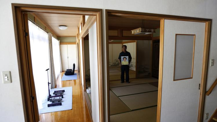 Watanabe holds a portrait of his late wife Hamako as he poses for a photo at his home at Yamakiya district in Kawamata town, Fukushima prefecture