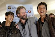 Director Sam French (C) and 14-year-old Afghan actors Fawad Mohammadi (L) and Jawanmard Paiz of the Oscar nominated live-action short film Buzkashi Boys, laugh together after arriving at Los Angeles International Airport (LAX) in Los Angeles, California February 20, 2013. The two stars of the movie were able to raise money for their trip from Afghanistan through a social fundraising website, and will attend the Academy Awards on February 24. REUTERS/Patrick Fallon