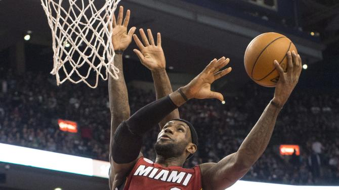 Miami Heat's LeBron James scores on Toronto Raptors' Amir Johnson during first half NBA basketball action in Toronto on Sunday, March 17, 2013. (AP Photo/THE CANADIAN PRESS,Chris Young)