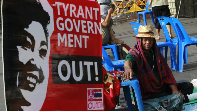 An anti-government protester rests next to a banner during a rally outside the Government House in Bangkok