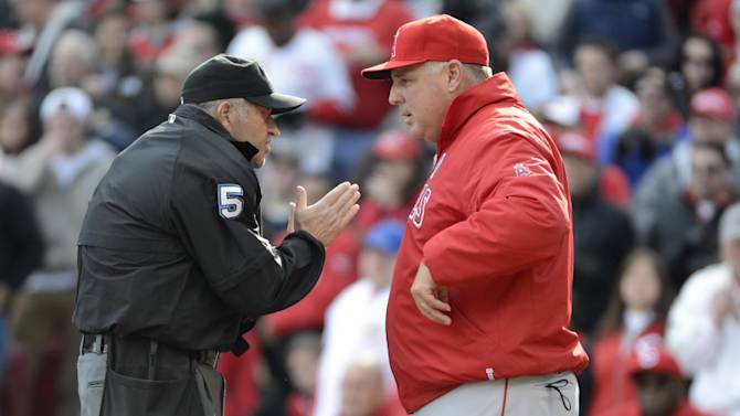 Los Angeles Angels manager Mike Scioscia questions a call at home plate with umpire Dale Scott (5) in the third inning of an opening day baseball game against the Cincinnati Reds, Monday, April 1, 2013, in Cincinnati. (AP Photo/Michael Keating)