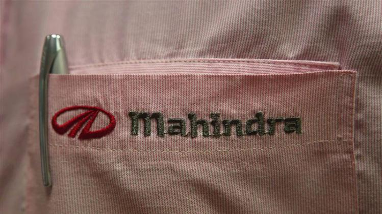 File picture shows the logo of Mahindra & Mahindra Ltd on the pocket of a salesman's shirt as he poses inside the company's showroom in Mumbai