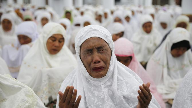Acehnese woman cries as she attends a mass prayer for the 2004 tsunami victims at Baiturrahman Grand Mosque in Banda Aceh