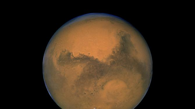 This Aug. 26, 2003 image made available by NASA shows Mars photographed by the Hubble Space Telescope on the planet's closest approach to Earth in 60,000 years. Mars is set to get its latest visitor Sunday, Aug. 5, 2012, when NASA's new robotic rover, named Curiosity, attempts to land there. Mars has been a prime target for space exploration for decades, in part because its climate 3.5 billion years ago is believed to have been warm and wet, like early Earth. (AP Photo/NASA)