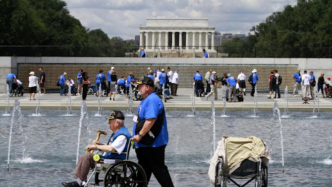 FILE - In this Wednesday, June 6, 2012 file photo, retired Army Infantry Pfc. Marvin Kincaid, 85, of Thayer, Mo., left, is accompanied by Dennis Hobbs at the the World War II Memorial in Washington as honor flight WWII veterans and helpers wearing blue or white t-shirts, visited the site on the 68th anniversary of D-Day. The Lincoln Memorial is in the background. As many as 100 World War II veterans missed their chance to travel to Washington to see their war's memorial after about $110,000 disappeared from a Kansas nonprofit that organized free trips for them. Central Prairie Honor Flights program director, LaVeta Miller, was charged in October 2012 with two counts of theft by deception. (AP Photo/Jacquelyn Martin)