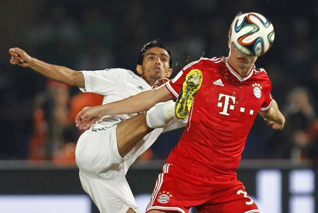 Chtibi of Morocco's Raja Casablanca fights for the ball with Kroos of Germany's Bayern Munich during their 2013 FIFA Club World Cup final soccer match at Marrakech stadium