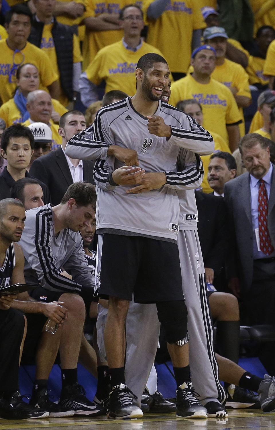 San Antonio Spurs power forward Tim Duncan, foreground, and shooting guard Tracy McGrady celebrate during the fourth quarter of Game 6 of a Western Conference semifinal NBA basketball playoff series against the Golden State Warriors in Oakland, Calif., Thursday, May 16, 2013. (AP Photo/Jeff Chiu)
