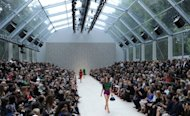 Models present creations during the Burberry Prorsum 2013 spring/summer collection catwalk show at London Fashion Week. Burberry dazzled a star-studded crowd with colourful metalics, corsets and capes despite a gloomy profit warning
