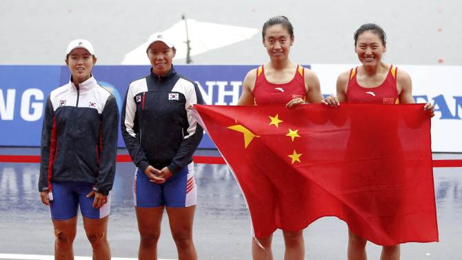 China's Zhang and Miao hold their national flag after winning the final of the women's pair event of the rowing competition at the Chungju Tangeum Lake International  Rowing Center, during the 17th Asian Games in Incheon