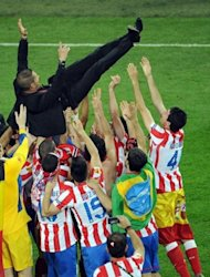 Atletico Madrid's players throw in the air their Argentinian coach Diego Simeone after winning the UEFA Europa League final football match between Atletico Madrid and Athletic Bilbao at the National Arena stadium in Bucharest