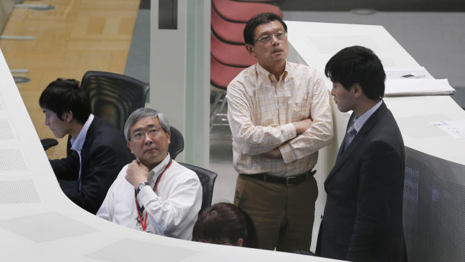 Workers of the Tokyo Stock Exchange look at monitors at a morning trading session in Tokyo, Friday, April 5, 2013. Japan's benchmark stock index hit 13,000 for the first time in more than four years Friday, a day after the country's central bank announced aggressive action to lift the economy out of an extended slump. (AP Photo/Koji Sasahara)