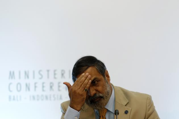 India's trade minister Sharma adjusts his hair during a news conference at the ninth WTO Ministerial Conference in Nusa Dua