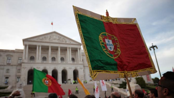 Demonstrators hold Portuguese flags outside the parliament in Lisbon at the end of a protest march against unemployment organized by workers' unions Saturday, Oct. 13 2012. Unemployment figures in Portugal have soared since the introduction of austerity measures to fight the country's debt crisis.  (AP Photo/Armando Franca)
