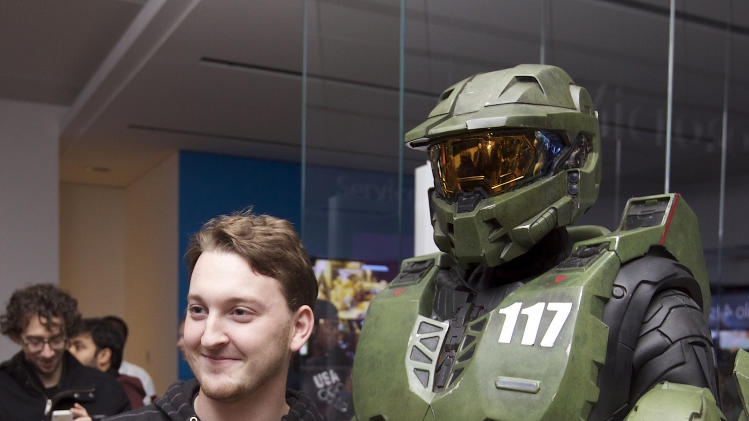 IMAGE DISTRIBUTED FOR XBOX - Peter Gagnon of Seattle poses for photos with Halo character Master Chief after purchasing the first copy of Halo 4 during the game's launch on Tuesday, Nov. 6, 2012 in Seattle. (Photo by Stephen Brasher/Invision for Xbox/AP Images)