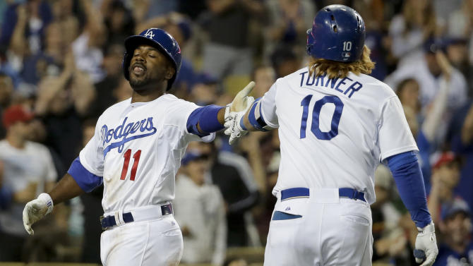 Los Angeles Dodgers' Jimmy Rollins, left, celebrates with Justin Turner after scoring on a hit by Howie Kendrick  during the sixth inning of a baseball game against the Philadelphia Phillies in Los Angeles, Monday, July 6, 2015. (AP Photo/Chris Carlson)