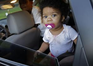 Amiyah Harvey, 18 months, sits in the back seat as…